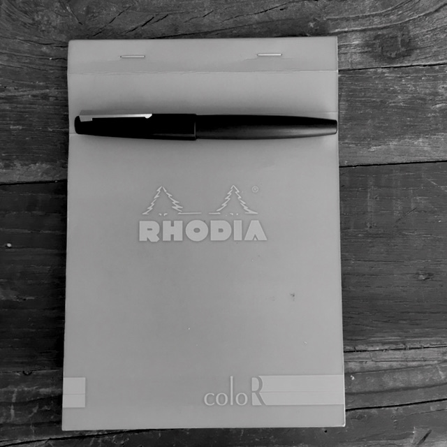 A blue Rhodia notebook and pen